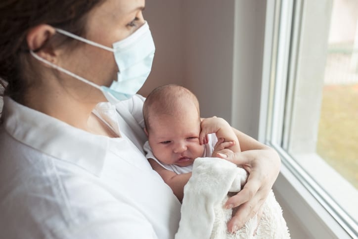 Mother with protective mask holding her baby daughter