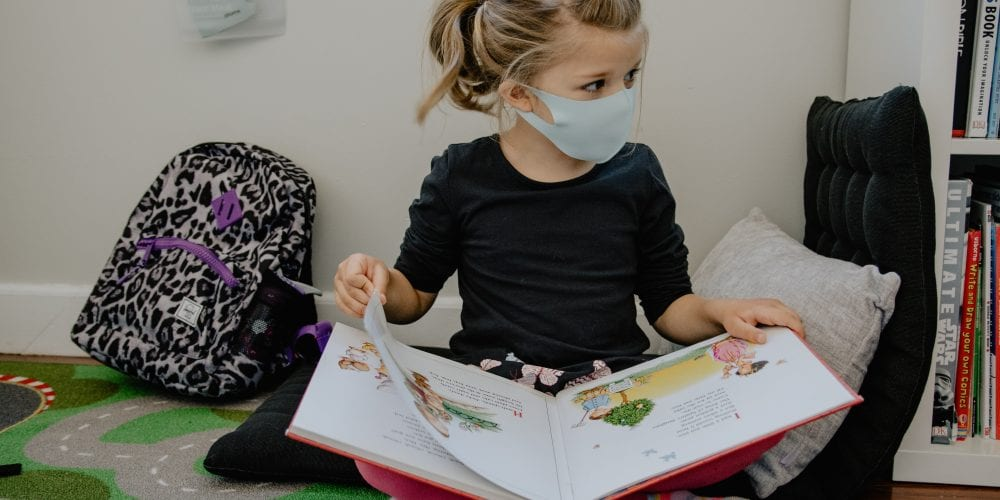 girl with mask on and backpack reading a book