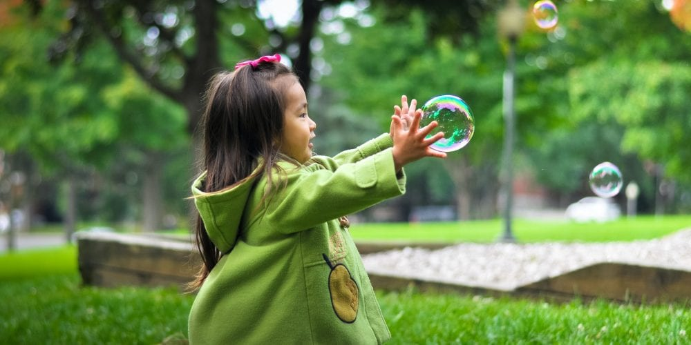 selective photo of a girl holding bubbles