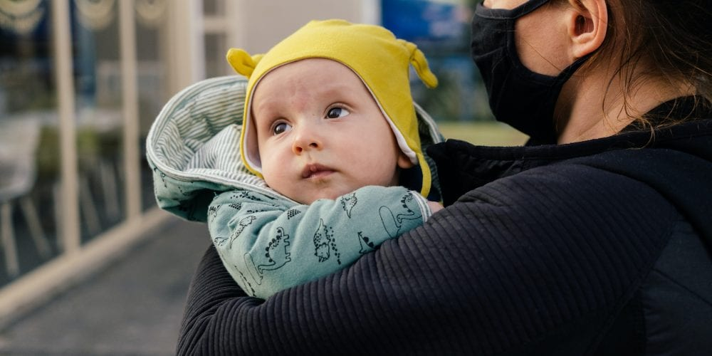 woman in black long sleeve shirt carrying baby in yellow knit cap